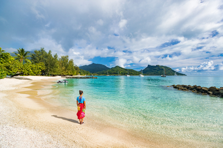 Travel tourist woman at French Polynesia beach on Huahine island cruise excursion on Tahiti holiday vacaton. Girl wearing polynesian sarong cover-up swimwear relaxing walking on sand.