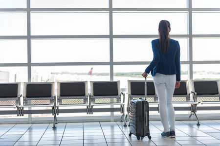 Travel tourist waiting at airport lounge with suitcase at tarmac window. Unrecognizable woman looking at lounge looking at airplanes while waiting at boarding gate before departure. Travel lifestyle.