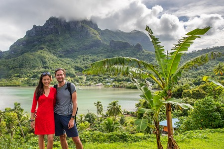 Bora Bora luxury cruise travel vacation tourists couple in front of Mt Otemanu in French Polynesia. Tahiti getaway holiday people visiting the island during cruise excursion tour. 스톡 콘텐츠
