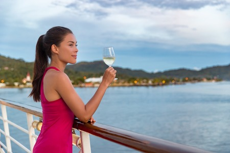 럭셔리 크루즈 선박 휴가 우아한 여자가 저녁 식사에서 즐기는 바다보기 보트에서 샴페인 한 잔. 빨간 드레스 갑판 야외 휴식에 아시아 아가씨. 스톡 콘텐츠