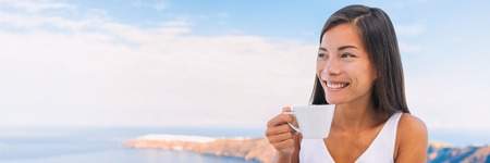 Woman drinking coffee at morning breakfast banner. Happy Asian girl holding cup of tea looking at holiday sea view with sky background. Panoramic crop.