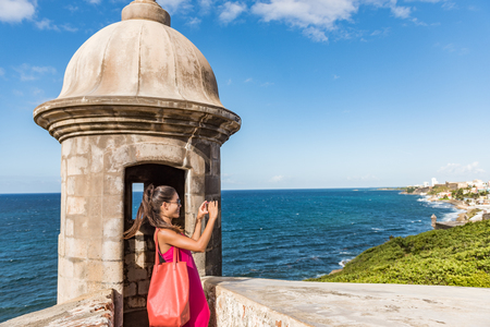 Puerto Rico San Juan woman taking phone pictures of Old San Juan Fort Castillo San Felipe Del Morro. Asian tourist people traveling in the USA visiting famous latin american landmark.