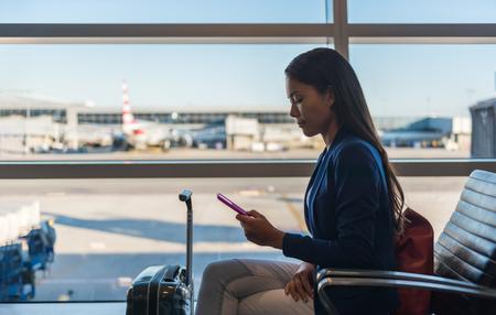 공항 전화 여행 여자 비즈니스 클래스에서 휴대 전화를 사용 하여 비행기 비행을 기다리고 라운지 문자 메시지 sms 메시지 스마트 폰입니다. 기술과 여