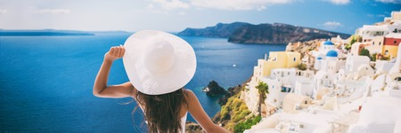 Luxury travel vacation woman in Santorini banner. Europe cruise ship destination holiday tourist looking at sea view with sun hat in Oia, Greece.
