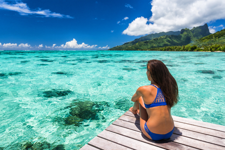Travel vacation bikini woman at luxury resort overwater villa in Tahiti. Cruise ship destination, exotica holiday island. Girl from behind relaxing sunbathing looking at ocean, tanned body.
