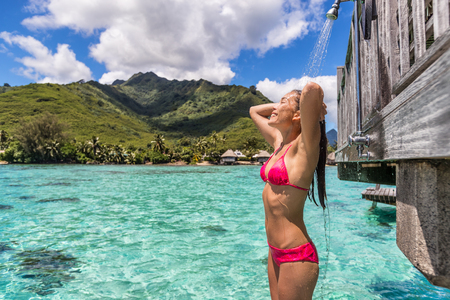 Luxury travel destination bikini woman taking an outdoor shower at luxury resort hotel overwater bungalow in Tahiti. Vacations in paradise Asian girl showering after swim. Stock Photo