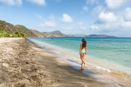 Cruise tourist visiting St Kitts island on a Caribbean travel holiday. Bikini woman walking relaxing at South Frigate Bay beach in St Kitts.