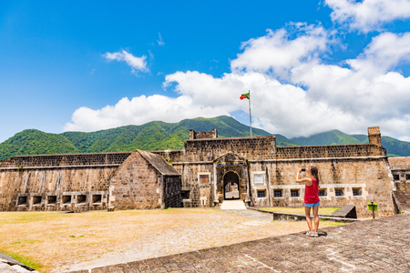 Cruise tourist at St Kitts Brimstone Hill Fortress on vacation on St Kitts and Nevis. Caribbean cruise ship destination. Girl standing taking photo using smart phone camera on holidays. 写真素材