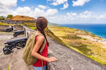 Tourist girl on St Kitts island cruise travel destination visiting Brimstone Hill Fortress National Park on vacation. Caribbean cruise ship woman walking on cannon lookout on summer holidays.
