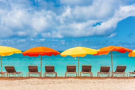비치의 자 및 우산 휴가 배경 - 신화 마틴 해변, 네덜란드 령 안틸레스, 카리브 섬의 모래에 줄 지어 다채로운 파라솔. 열 대 휴가 여행 풍경입니다. 스톡 콘텐츠