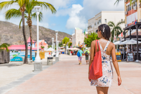 Philipsburg St Maarten woman tourist walking in shopping street, cruise ship travel destination. Caribbean tropical island hopping vacation holiday. Girl with purse bag visiting town. Stock Photo