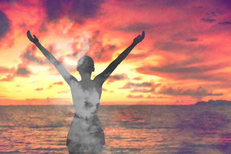 自由な女性ダブル露出雲は、ウェルネスと禅で開かれた腕で瞑想空の夕日。瞑想の概念。 写真素材