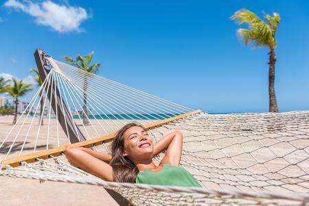 Strandvakantie vrouw gelukkig slapen in hangmat op vakantieoord - Caribische reisvakanties Aziatisch meisje liggen buiten ontspannen zonnen.