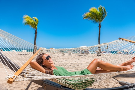 Beach relaxation sun tanning girl lying down on hammock relaxing sunbathing in Caribbean vacation holiday at resort hotel. Happy woman in sunglasses and cover-up dress laid back enjoying suntan. Stockfoto