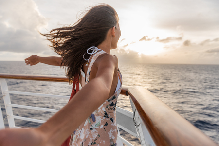 Cruise ship vacation travel woman enjoying freedom. Holiday tourist with open arms in front of boat feeling carefree in the tropical wind .