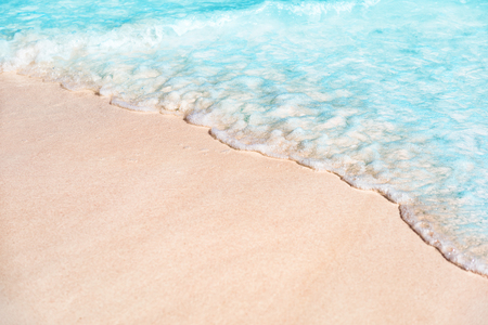 Beach background copy space of water wave tide over white sand texture. Turquoise ocean sea tropical travel vacation concept.