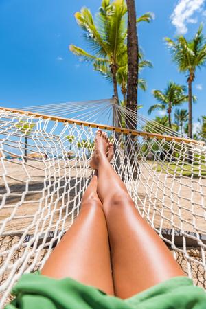 ビーチハンモックバケーション女性足の自分撮り。熱帯の夏の目的地で日焼け彼女の足と足のポブ写真を撮ってリラックスした女の子。旅行楽しい 写真素材