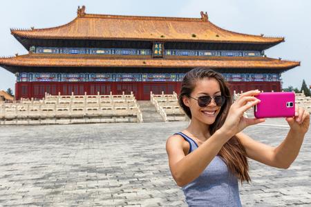Gelukkige toerist die smartphonebeeld op de reis van Azië nemen tijdens de zomer in China. Jonge vrouw die zonnebril draagt die selfies foto's met mobiele telefoon doen. Stockfoto