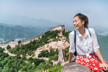 Young woman tourist on Great wall of china, Asia tourism summer travel. Happy young multiracial girl visiting famous Beijing tourist attraction with backpack, popular destination. Stock Photo