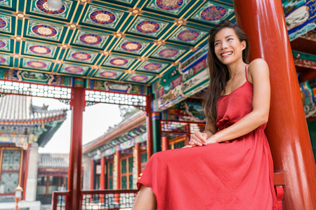 Beautiful asian young woman relaxing on summer holiday by ancient traditional wooden red door in Chinese temple on china travel destination. Girl tourist in elegant silk sun dress.