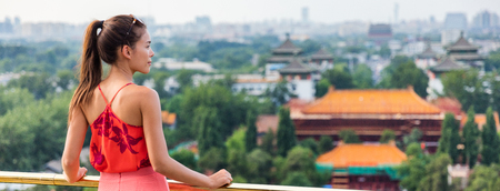 China summer travel banner woman in Asia. Chinese tourist relaxing looking at view of famous chinese landmark, the forbidden City in Beijing. Banco de Imagens