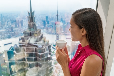 Asian woman drinking hot cup of afternoon tea while looking at view of landmark skyscraper building in Lujiazui, Pudong, Shanghai city, China. Chinese tourist relaxing looking at window.