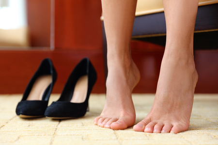 High heels shoes and feet closeup. Woman taking off stilettos resting barefoot for comfort at home or at shopping store trying new fashion footwear.