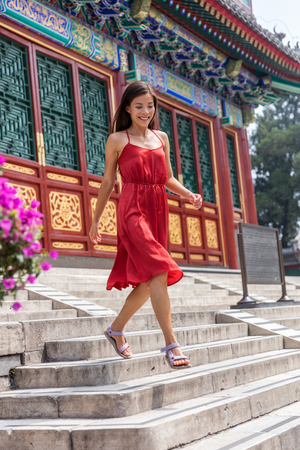 Beautiful young Asian woman walking down the stairs of an old chinese temple, traditional tourist attraction during china summer travel. Girl tourist in Beijing. Stock fotó