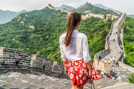 Young girl tourist from behind looking at view of Great Wall of china at famous Badaling tourism attraction during travel vacation in Beijing. Asia summer holidays. Stock Photo