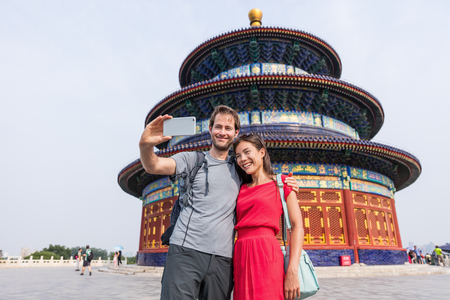 Happy couple travelers taking selfie picture together at temple of heaven during china summer travel. Young multiracial people using phone photography app for photos.