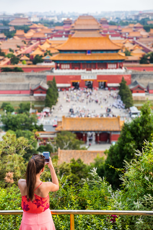 china summer travel. Woman tourist taking pictures with mobile phone of aerial view of imperial palaces, old temples, the forbidden City in Beijing, china. Jingshan Gongyuan park.