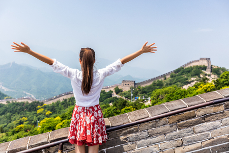 Happy cheerful tourist woman at Great Wall of china having fun un arms outstretched on travel during vacation trip in Asia. Girl visiting and sightseeing Chinese destination in Badaling