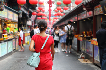 Woman tourist walking in chinatown on china travel. Asian girl on Wangfujing food street during Asia summer vacation. Traditional Beijing snacks being sold at chinese chinatown outdoor market.