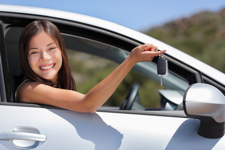 New car driver woman holding keys for travel road trip. Happy young Asian girl with rental lease or purchase of automobile at dealership.