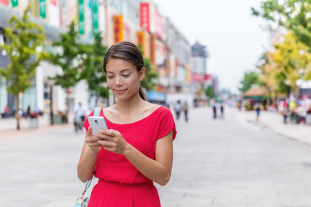 Asian woman outside on Wangfujing shopping street in Beijing, china, using mobile phone app to shop online. Happy Chinese woman texting sms on smartphone.