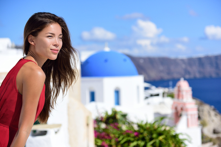 Santorini woman Europe cruise travel vacation. Tourist Asian beauty girl relaxing looking at view of three blue domes, Oia island, Greece, famous Europe cruise destination.