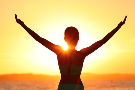 Freedom woman with open arms silhouette in sunrise against sun flare. Morning yoga girl practicing sun salutation outdoors. Carefree person living a free life. Success freedom happy life concept.