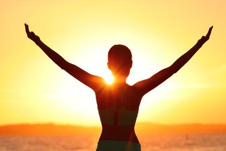 Vrijheidsvrouw met open wapenssilhouet in zonsopgang tegen zongloed. Ochtendyoga meisje het beoefenen van zon aanhef buitenshuis. Zorgeloze persoon die een vrij leven leidt. Succes vrijheid gelukkig leven concept.