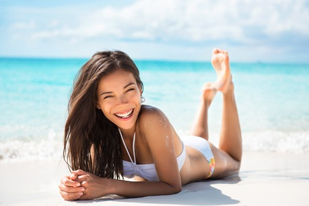 Happy healthy beautiful Asian multiracial woman lying down on sand enjoying sun tanning sunbathing in swimsuit relaxing on Caribbean tropical beach summer vacation. Smiling laughing girl. Фото со стока