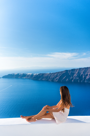 Luxury travel vacation Europe tourist woman relaxing at fancy hotel resort balcony in greek Santorini island, Greece with view over the Mediterranean Sea and Oia.