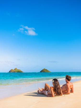 Tiri la coppia in secco rilassandosi prendendo il sole sulla spiaggia tropicale hawaiana in Lanikai, Oahu, Hawai, USA Popolo americano su abbronzatura sole vacanze estive sdraiato sulla sabbia. Archivio Fotografico - 93554528