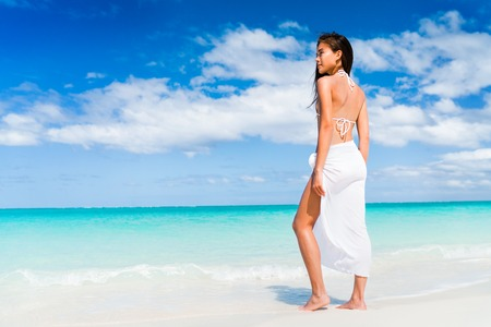 Elegant Asian woman in white beachwear bikini and fashion sarong standing on beach. Luxury travel vacation. Swimsuit swimwear model girl on summer holiday in the Caribbean. 版權商用圖片