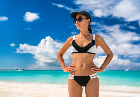 Asian bikini woman on beach summer vacation sporty swimwear girl in sportswear for beach sports. Athlete with fit body wearing solar protection hat and sunglasses, skin care. Stock Photo