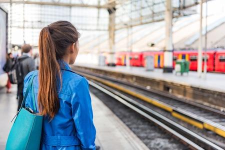 駅の朝の通勤女性は、電車が到着するのを待って仕事に行きます。公共交通機関のプラットフォーム上の人々.ラッシュアワーで通勤。ビジネスマン 写真素材