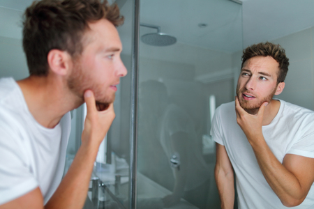 Man face care looking in mirror touching his beard or skin health. Male beauty morning skincare routine in home bathroom. After shave men lifestyle concept.