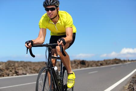 Road bike cyclist man sport athlete training cardio workout on racing bicycle. Male biker biking outdoors training for triathlon. Archivio Fotografico