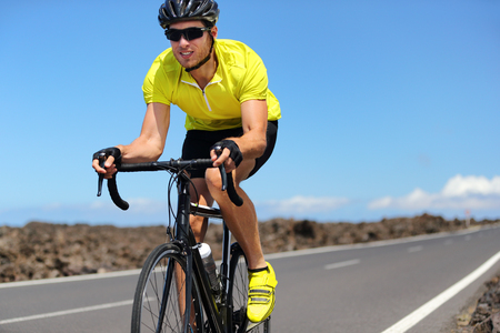 Road bike cyclist man sport athlete training cardio workout on racing bicycle. Male biker biking outdoors training for triathlon. Foto de archivo