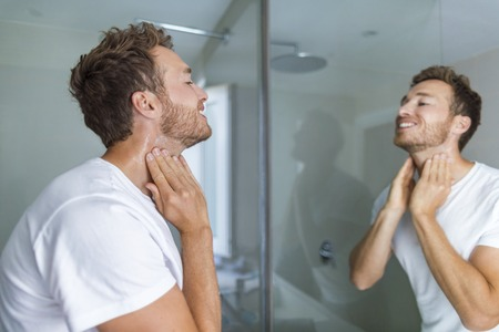 Man putting after shave perfume lotion or skin care cream for sensitive skin after shaving beard looking in bathroom mirror on neck. Male beauty, beard care skincare concept.