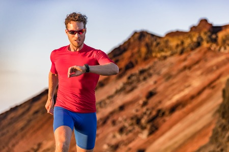 Athlete runner checking cardio on sports smartwatch jogging on outdoor run track. Running man wearing sunglasses and tech wearable device looking at watch during training workout. Stock Photo