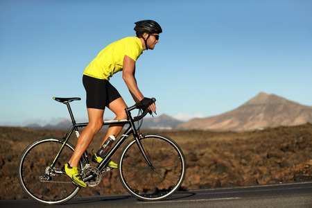 Biking cyclist male athlete going uphill on open road training hard on bicycle outdoors at sunset. Nature landscape.